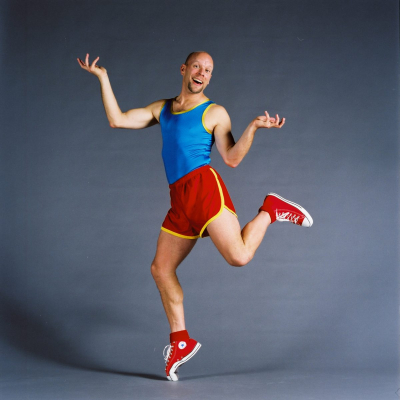 Bald man in bright athletic clothing humorously balances on one toe.