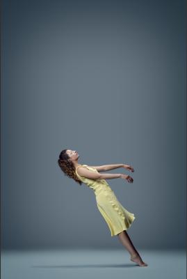 Dancer in a yellow dress falls backwards.