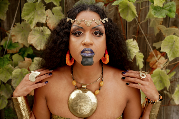 Brown skinned woman adorned in African gold jewelry and black paint.