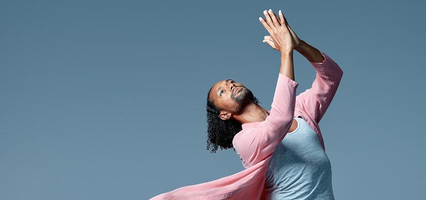 Dancer in pink coat raises their hands in prayer