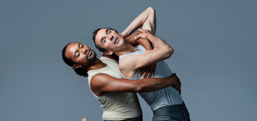 dancers embrace while bending backwards over a chair