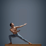 Marte lunges sideways on top of a wooden bench, with his arms and focus stretching upwards to his left. His hands are supinated, as if receiving the faint glow that is above. He is shirtless and in blue leggings.