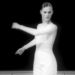 Lady in white swings arms. Photo is black and white.