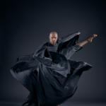 bald man in billowing dark cloak fiercely kicks his leg out to the side