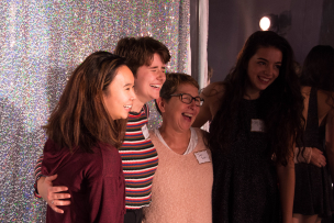 The chair of the dance department posing and laughing for a photo with three dance students at the Fall for Dance party