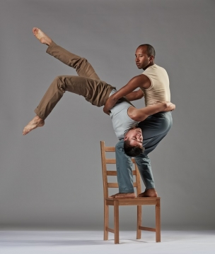 Jo stands on a chair while holding Fausto that is upside down.
