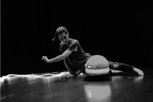 A woman dances on the floor with a small robot