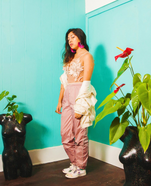 A queer mixed- Filipinx dancer poses between two plants infront of an aqua painted wall