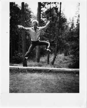 Douglas Dunn jumping high infront of tree trunks