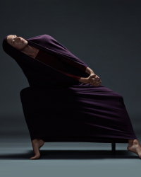 dancer in purple cloth leans over