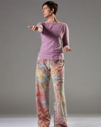 Julia stands face on in colorful pants. Her right arm is extended straight forward while her left arm is bent at the elbow near her hip. Her left knee is slightly bent and she looks to her right.