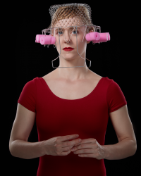 Lady in red shirt and lipstick with wire basket and foam hair curlers on head.