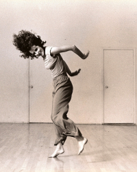 Trisha Brown flings her hair forward and her arms behind her