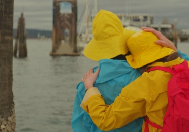 two in colorful raincoats and rain hats lean on each other on a dock