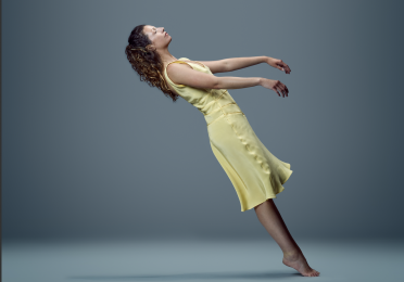 Dancer in a yellow dress falls backwards.