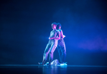 Two dancers lean back to back holding up flashlights