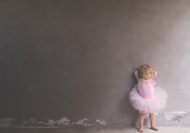 A little girl in ballet clothing standing at a wall