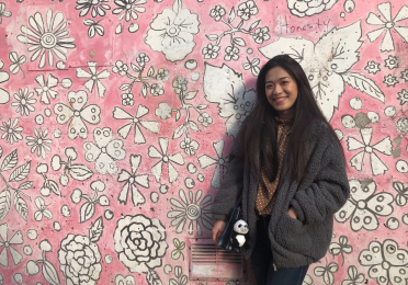Coco in front of a pink wall