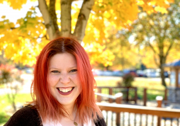 Tori Siddall smiles in front of yellow trees.