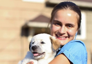 Ieva holds her dog and smiles