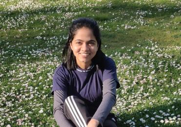 Sweekruthi sitting in a field