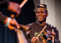 Etienne Cakpo plays percussion and smiles