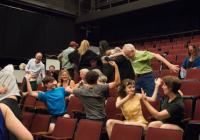 audience members wave their arms and wiggle their bodies as part of graduate symposium lecture.