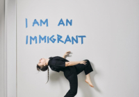 "Alice dances front of a wall that says, ""I am an immigrant"""