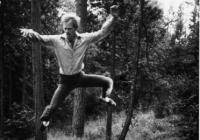 Douglas Dunn jumping high infront of tree trunks