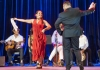 Monica Rojas Stewart dancing in a red dress with a partner and handkerchief