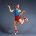 Bald man in bright athletic clothing humorously balances on one toe.