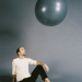 A man sits casually on the floor staring the large sphere that is floating above.